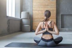 Giovane donna nella classe di yoga, posa inversa di preghiera Fotografie Stock