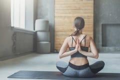 Giovane donna nella classe di yoga, posa inversa di preghiera Fotografie Stock Libere da Diritti