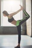 Giovane donna nella classe di yoga, signore rilegato della posa di ballo Fotografia Stock Libera da Diritti