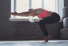 Giovane donna nella classe di yoga, transizione di vinyasa alla posa Fotografia Stock Libera da Diritti