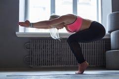 Giovane donna nella classe di yoga, transizione di vinyasa alla posa Immagine Stock