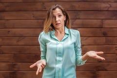Giovane donna nella condizione della blusa isolata sulle mani della parete da parte sconcertanti immagine stock