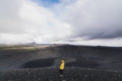 Giovane donna nella condizione gialla dell'impermeabile nel cratere del vulcano nell'area di Myvatn, Islanda di Hverfjall fotografia stock