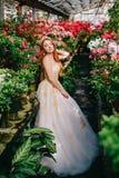 Giovane donna nella condizione lussuosa del vestito nel giardino fiorito fotografie stock libere da diritti