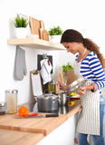 Giovane donna nella cucina che prepara un alimento Immagini Stock