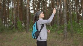 Giovane donna nella foresta che prova a prendere un segnale mobile archivi video