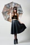 Giovane donna nella maschera del partito con l'ombrello Fotografia Stock
