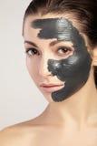 Giovane donna nella maschera per il fronte dell'argilla nera Immagine Stock