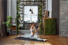 Giovane donna nella posa di pratica di yoga dell'equilibrio del homeware su tappeto nella sua camera da letto comoda Immagine Stock Libera da Diritti