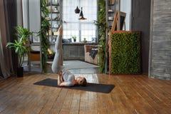 Giovane donna nella posa di pratica di yoga dell'equilibrio del homeware su tappeto nella sua camera da letto comoda Fotografie Stock