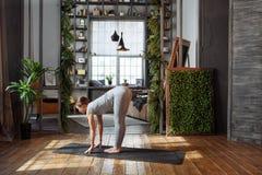 Giovane donna nella posa di pratica di yoga dell'equilibrio del homeware su tappeto nella sua camera da letto comoda Immagini Stock