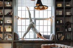 Giovane donna nella posa di pratica di yoga dell'equilibrio del homeware su tappeto nella sua camera da letto comoda Fotografia Stock Libera da Diritti