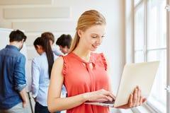 Giovane donna nella riunione che lavora al suo computer portatile Fotografia Stock