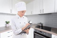 Giovane donna nella scrittura dell'uniforme del cuoco unico qualcosa in lavagna per appunti nel Mo immagini stock