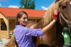 Giovane donna nella stalla con il cavallo fotografia stock