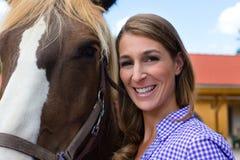 Giovane donna nella stalla con il cavallo in sole Immagini Stock