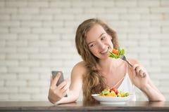Giovane donna nelle posizioni allegre con l'insalatiera dal lato fotografia stock