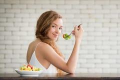 Giovane donna nelle posizioni allegre con l'insalatiera dal lato immagine stock