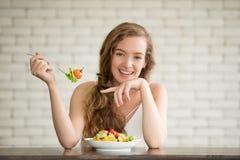 Giovane donna nelle posizioni allegre con l'insalatiera dal lato fotografie stock