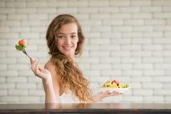 Giovane donna nelle posizioni allegre con l'insalatiera dal lato fotografia stock libera da diritti
