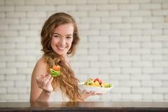 Giovane donna nelle posizioni allegre con l'insalatiera dal lato immagini stock libere da diritti