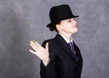 Giovane donna nello stile virile con il mini sigaro su fondo grigio, la ragazza nel vestito e nel legame del ` s dell'uomo, la ca Fotografia Stock