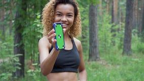 Giovane donna nera che utilizza il suo smartphone in una rottura pareggiare e dalle manifestazioni lo schermo nella macchina foto