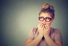 Giovane donna nerd sollecitata nervosa in vetri che morde le unghie che guardano ansiosamente immagine stock libera da diritti