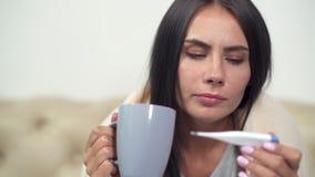 Giovane donna non sana che tiene un termometro stock footage