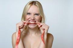 Giovane donna nuda che morde un nastro di misurazione fotografia stock