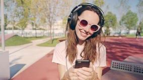 Giovane donna o adolescente sorridente e di risata con lo smartphone e le cuffie che ascolta la musica nel parco o sul stock footage