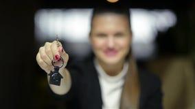 Giovane donna o agente immobiliare sorridente felice di affari che mostra le chiavi dalla nuova casa Isolato sopra fondo Fuoco so video d archivio