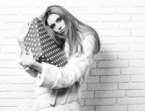 Giovane donna o ragazza graziosa alla moda con bei capelli biondi lunghi in cappotto della vita di pelliccia bianca e di modo immagini stock libere da diritti