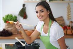 Giovane donna o studente ispanica che cucina nella cucina Fotografia Stock Libera da Diritti