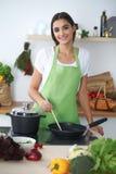 Giovane donna o studente ispanica che cucina nella cucina Fotografie Stock Libere da Diritti