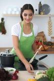 Giovane donna o studente ispanica che cucina nella cucina Fotografia Stock