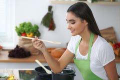 Giovane donna o studente ispanica che cucina nella cucina Immagine Stock