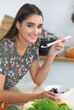 Giovane donna o studente ispanica che cucina nella cucina Ragazza che assaggia insalata fresca mentre sedendosi alla tavola Fotografia Stock