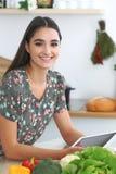 Giovane donna o studente ispanica che cucina nella cucina Ragazza che per mezzo della compressa per fare acquisto online o per tr Immagini Stock