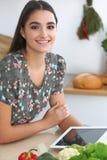Giovane donna o studente ispanica che cucina nella cucina Ragazza che per mezzo della compressa per fare acquisto online o per tr Fotografie Stock Libere da Diritti