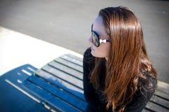 Giovane donna in occhiali da sole che si siedono ad un banco del molo Fotografia Stock