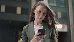 Giovane donna in occhiali da sole rossi che esaminano il suo smartphone che sta in via della città video d archivio