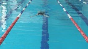 Giovane donna in occhiali di protezione e stile del colpo di rana di nuoto del cappuccio nello stagno dell'interno della corsa de archivi video