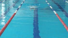 Giovane donna in occhiali di protezione e stile del colpo di rana di nuoto del cappuccio nello stagno dell'interno della corsa de video d archivio