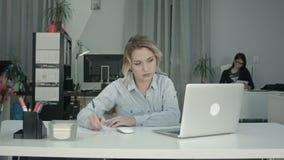 Giovane donna occupata che lavora al computer portatile nell'ufficio mentre il suo collega che per mezzo della compressa stock footage