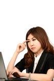 Giovane donna occupata di affari che lavora allo scrittorio che scrive su un computer portatile Fotografie Stock Libere da Diritti