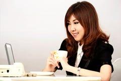 Giovane donna occupata di affari che lavora allo scrittorio che scrive su un computer portatile Fotografia Stock