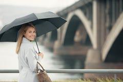 Giovane donna in ombrello blu della tenuta del cappotto immagine stock libera da diritti