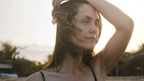 Giovane donna pacifica attraente del viaggiatore con i capelli di volo che posano con lo sguardo calmo alla spiaggia esotica di s video d archivio