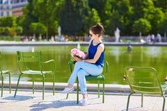 Giovane donna parigina con le peonie rosa in Tuileries Fotografia Stock
